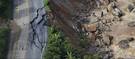 Funcionários trabalham em estrada destruída, em Nova Friburgo
