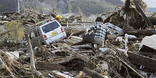 Após tremor, pessoa tenta passar por destroços na região de Iwate